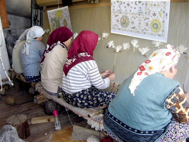 "This is as close as we come to ""factory"" rugs.  These women weave for Umit, who makes our Usak carpets."